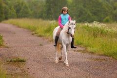 Småbarnridning på en vit häst på vägen utomhus Arkivbild