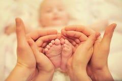 Småbarns fot i händerna av föräldrar Arkivbilder