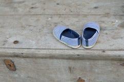 Småbarns skor med sand Arkivbild