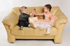 Småbarnsammanträde på sofaen med en gåva boxas Royaltyfria Bilder
