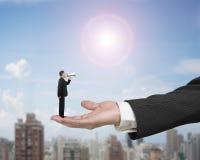 Småföretagare som använder högtalaren som ropar på den stora manliga handen Royaltyfri Bild