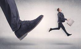 Småföretagare som sparkas av den stora skon arkivbilder