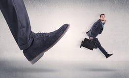 Småföretagare som sparkas av den stora skon royaltyfria foton