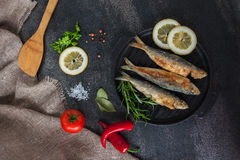 Småfisksardiner stek, broi, gallerfisk på den järn- stekpannan med grönsaker och kryddor omkring Arkivfoto