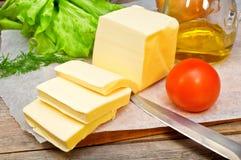 Smör i pergamentpapper och grönsaker Arkivfoton