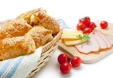 Smördegsmå pastejer med ostskinkasesam och körsbärsröda tomater royaltyfria bilder