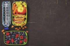 Smörgås, äpple, druva, morot, bär i plast- lunchask och b Arkivfoto