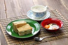 Smörgås för Kaya driftstopprostat bröd med en kopp av vitt kaffe royaltyfri foto