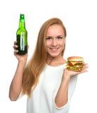 Smörgås för kvinnahållhamburgare i hand och flaska av öl arkivfoton
