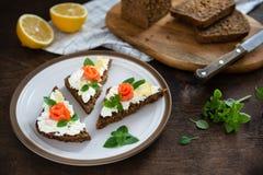 Smörgås för rökt lax med den ny kräm, citronen och basilika på den vita plattan sunt frukostbegrepp Wholegrain bröd, kopieringsut arkivfoto