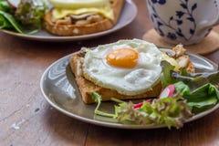 Smörgås i den vita maträtten på trätabellen Royaltyfria Bilder