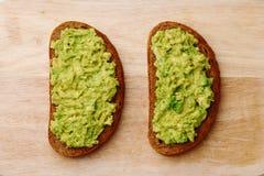 Smörgås med guacamole på guacamole för bästa sikt för träbakgrund på bröd arkivfoton