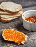 Smörgås med kaviaren för smör och för röd lax arkivbild