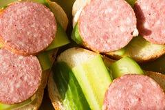 Smörgås med korven och en gurka Arkivfoto