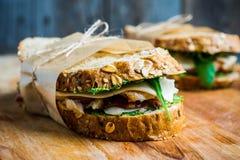 Smörgås med sädes- bröd, höna, pesto och ost på den lantliga träbakgrunden arkivfoton