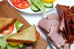 Smörgås med skinka, grönsallat, skivor av ost, tomater royaltyfria foton