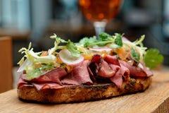 Smörgås med steknötkött på restaurangtabellen, närbild arkivfoto