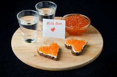 Smörgås tre med den röda kaviaren i form av en hjärta, vodka arkivbilder