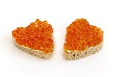 Smörgås två i form av en hjärta med röd kaviarvit Arkivfoto