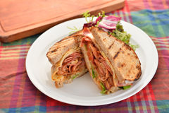 Smörgåsar av bacon och örter på den vita plattan på tabellen Royaltyfri Bild