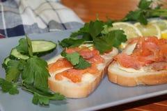 Smörgåsar av vitt bröd med den röda fisken och smör Royaltyfria Foton