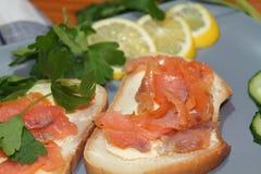 Smörgåsar av vitt bröd med den röda fisken och smör Arkivfoton