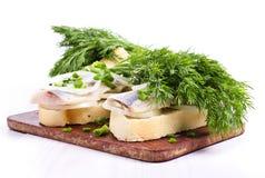 Smörgåsar av vitt bröd med sillen, lökar och örter Arkivfoton