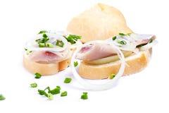 Smörgåsar av vitt bröd med sillen, lökar och örter Royaltyfria Bilder