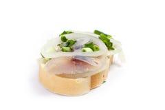 Smörgåsar av vitt bröd med sillen, lökar och örter Arkivfoto