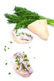 Smörgåsar av vitt bröd med sillen, lökar och örter Arkivbild