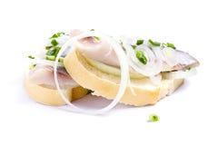 Smörgåsar av vitt bröd med sillen, lökar och örter Arkivbilder