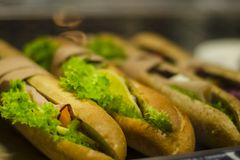 Smörgåsar/bagetter med grönsallat, skinka, ost på räknaren av flygplatsen på flygplatsen under exponeringsglas Skjutit i en studi royaltyfria foton