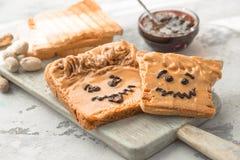 Smörgåsar för danandejordnötsmör med personlighet! Rolig smileyframsida som dras på med driftstopp Krämigt jordnötsmör med drifts arkivfoto