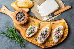 Smörgåsar med ätliga blommor för gräddost och för vitlök, olivgrönt bräde royaltyfria foton