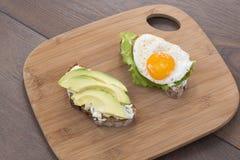 Smörgåsar med avokadot, ägget och grönsallat som förläggas på en skärbräda royaltyfria foton