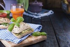 Smörgåsar med basilika och ost Bröd med sädesslag Ett exponeringsglas av morotfruktsaft Sund frukostservett i en blått bur och st arkivbild