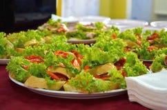 Smörgåsar med den röda fisken och grönsallat på vitt bröd under buffétabellen med servetter arkivbild