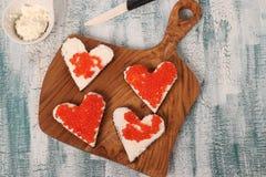 Smörgåsar med den röda kaviaren och gräddost i formen av en hjärta för valentin dag arkivfoto
