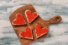 Smörgåsar med den röda kaviaren och gräddost i formen av en hjärta för valentin dag royaltyfri foto