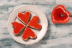 Smörgåsar med den röda kaviaren och gräddost i formen av en hjärta för valentin dag royaltyfria bilder
