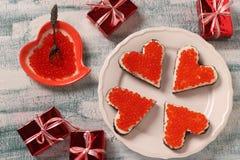Smörgåsar med den röda kaviaren och gräddost i formen av en hjärta för valentin dag royaltyfri bild