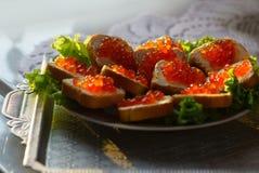 Smörgåsar med den röda kaviaren på en platta arkivbilder