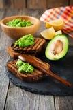 Smörgåsar med den traditionella mexicanska sås, avokadot och citronen för guacamole på gammal träbakgrund Arkivfoto
