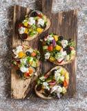Smörgåsar med feta, tomater, gurkor och oliv Grekisk salladbruschettastil på en lantlig skärbräda Royaltyfria Foton