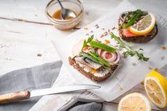 Smörgåsar med fisken och ingredienser på brädet arkivfoto