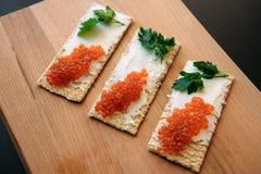Smörgåsar med kaviaren för röd lax och gräsplan på ett träbräde på en svart tabell, selektiv fokus royaltyfria bilder