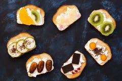 Smörgåsar med kräm- och olika frukter Sött rostat bröd med frukt på en blå bakgrund, bästa sikt En ram av söta smörgåsar Royaltyfri Foto