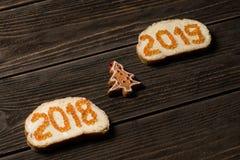 Smörgåsar med 2018 och 2019 röda kaviar på olika linjer med det lilla leksaksörja-trädet mellan arkivfoton