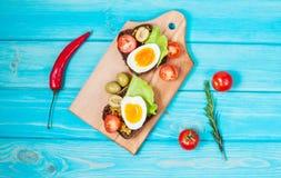 Smörgåsar med oliv, vaktelägg, körsbärsröda tomater och sallad på en träblueboard Royaltyfri Bild