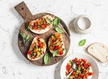 Smörgåsar med snabb ratatouille på lantlig skärbräda på en ljus bakgrund Läcker sund vegetarisk mat Arkivbilder